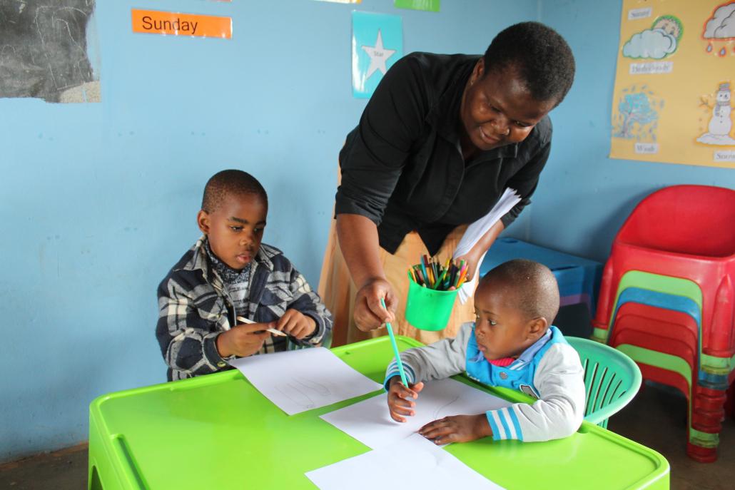 NCP Teacher handing over pens.