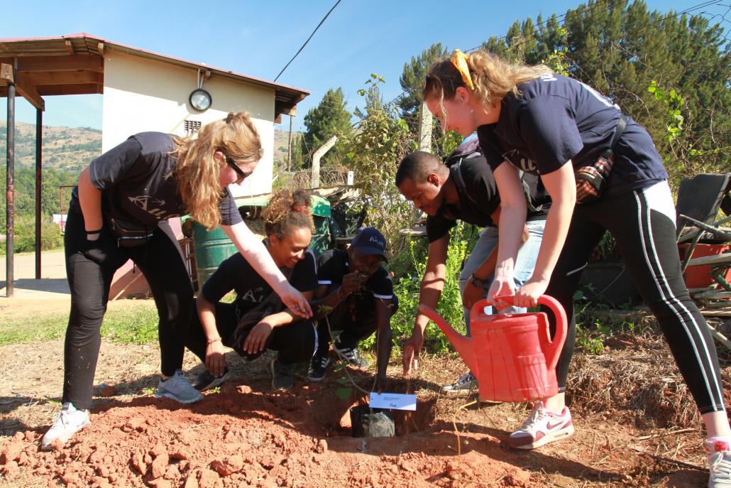 Simise with volunteers planting a tree during World Environment Day