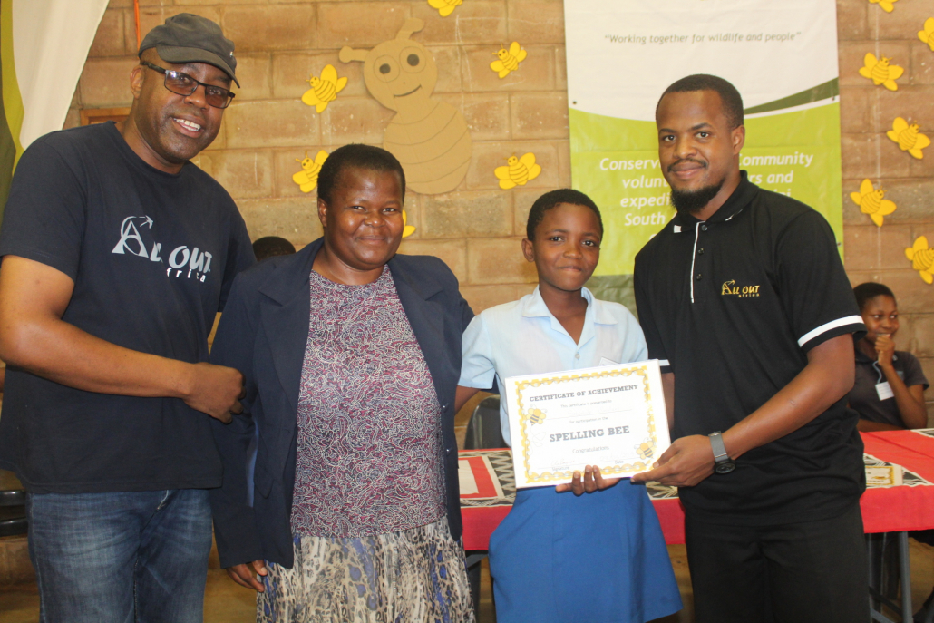 Tjengisa, NCP Teacher and Simise awarding a certificate to one of the homework club students.