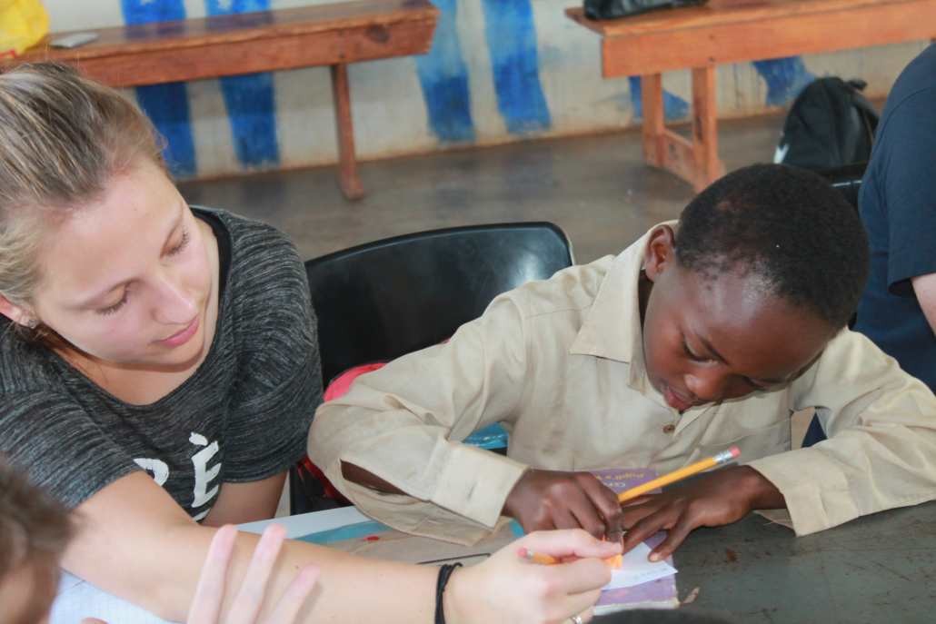 All Out Africa volunteer helping a primary school child with his school work.